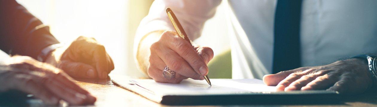 Person zeigt auf einem Blatt Papier einer anderen Person etwas.