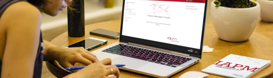 Person sitting in front of a laptop on which the page of the IAPM Project Managers' Guide is visible. [1]
