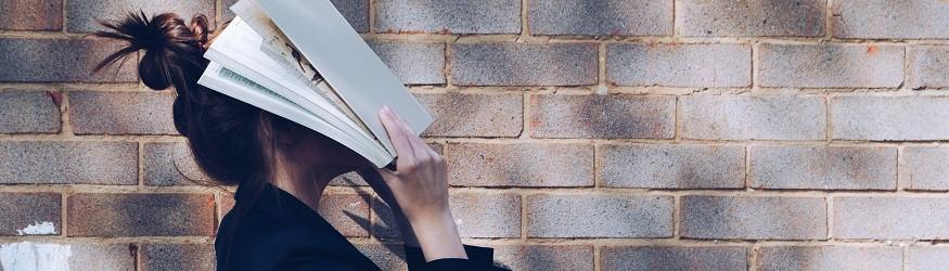 Frau hält Buch an ihr Gesicht. [1]